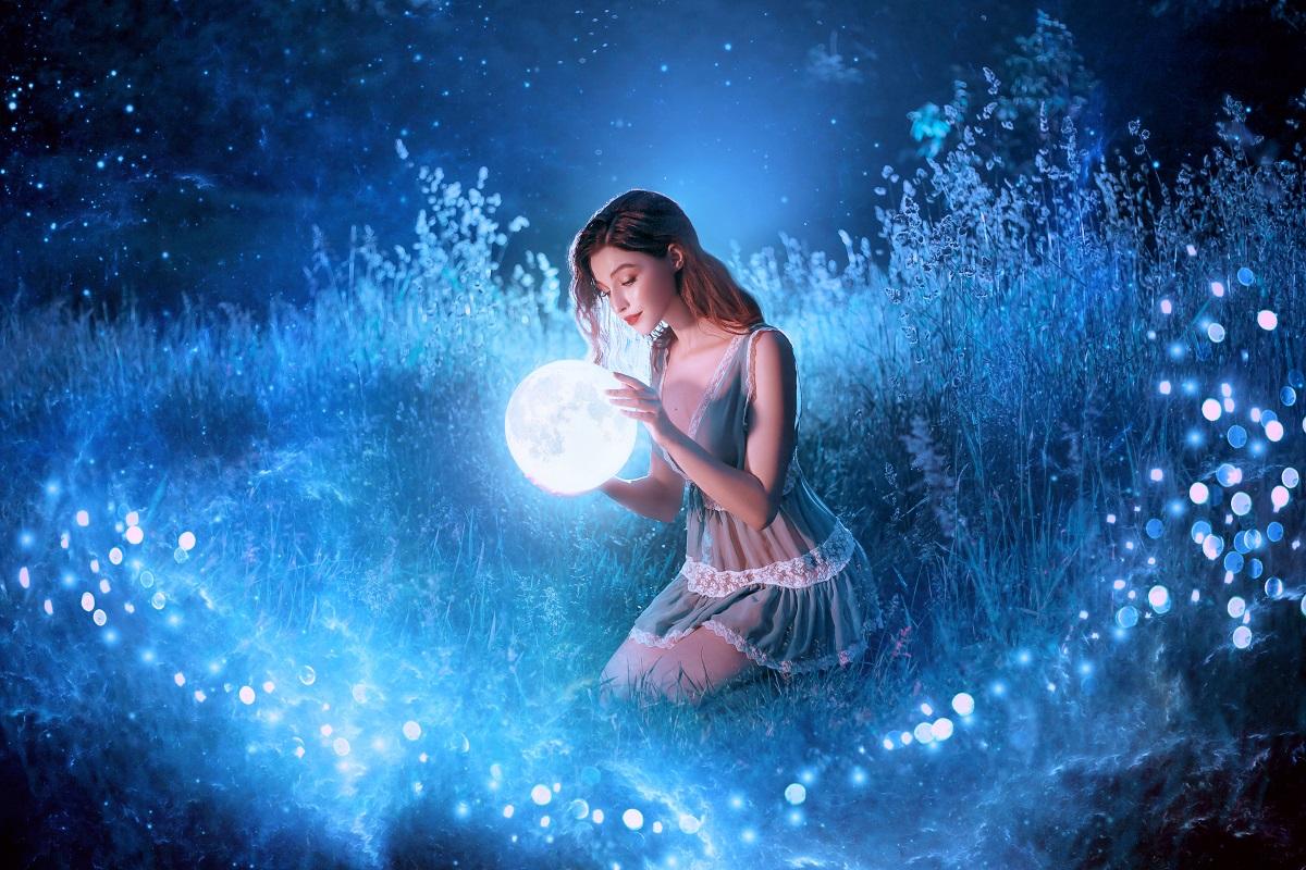 O femeie frumoasă care ține în mâini Luna Nouă în zodia Leilor și formează în jurul său o linie de lumină albastră