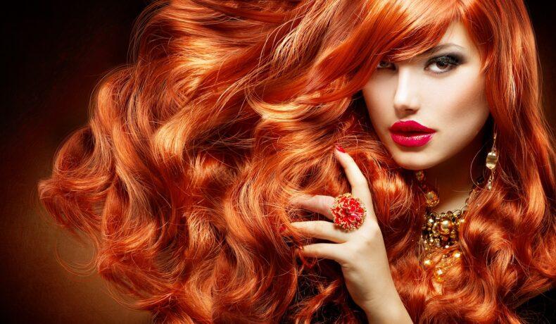 O femeie frumoasă cu un păr superb roșcat în timp ce privește intens la cameră și își trece mâna prin părul creț pe care a folosit una din acele măști naturale pentru părul vopsit