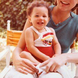 Meghan Markle bebeluș în timp ce zâmbește și stă în brațele unei femei