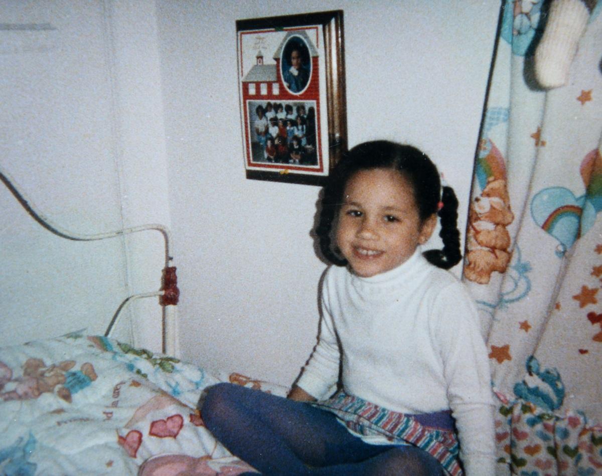 Meghan Markle într-o cameră cu un tablou în timp ce poartă o bluză abă și o pereche de blugi și are părul împlretit în codițe