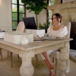 Meghan MArkle în timp ce stă la un birou din casa sa și privește la laptop