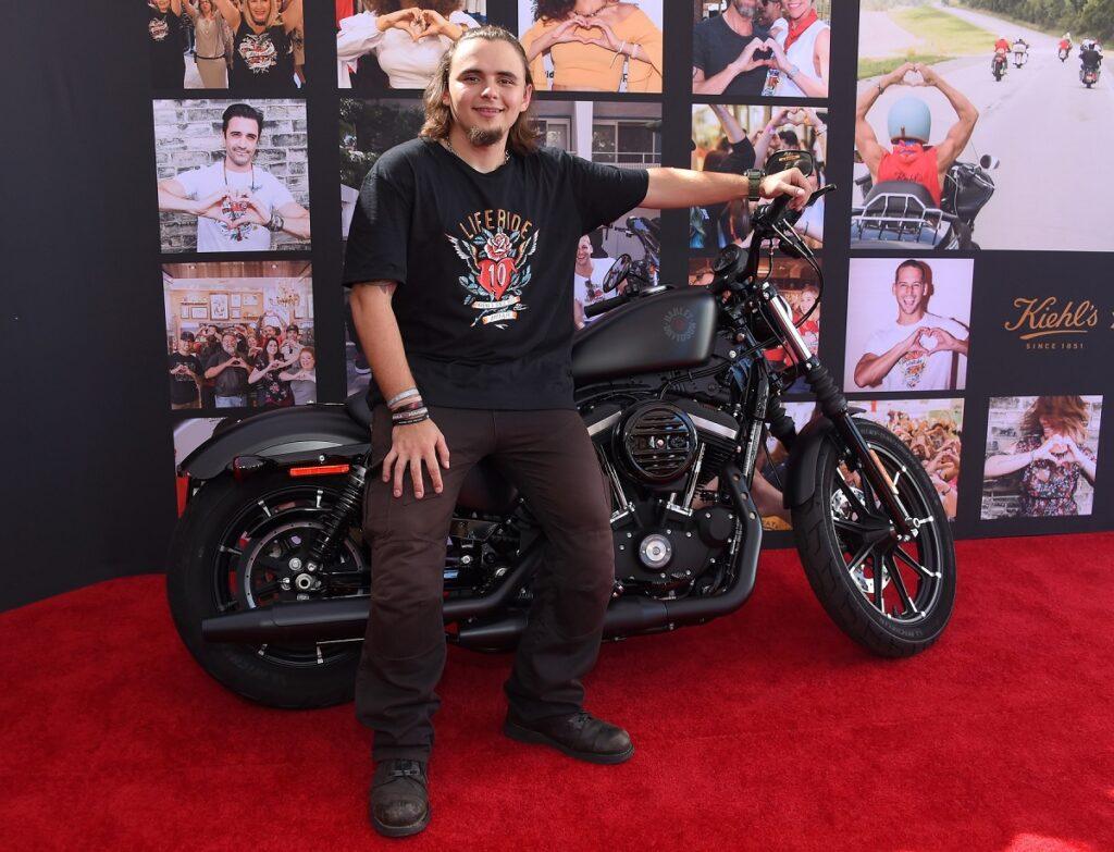 Michael Joseph 'Prince' Jackson Jr într-un tricou negru și cu o pereche de pantaloni maro în timp ce se sprijină de o motocicletă