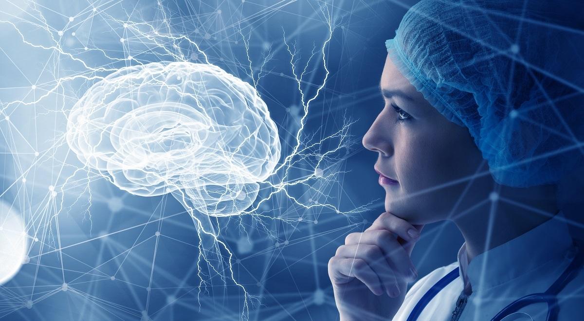 O femeie doctoriță care privește un creier luminat în timp ce se gângește la cauzele care duc la apariția demenței