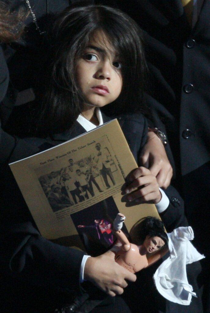 Prince Michael Blanket Jackson II, în timp ce ține în mână o revistă la ceremonia de înmormântare a tatălui său, Michael Jackson din 2009