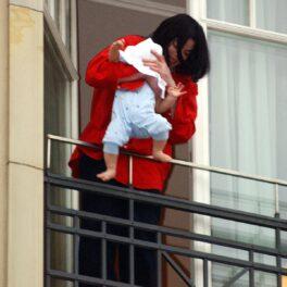 Michael Jackson într-o cămașă roșie în timp ce îl scoate pe Prince Michael 'Blanket' Jackson II pe un balcon în Berlin