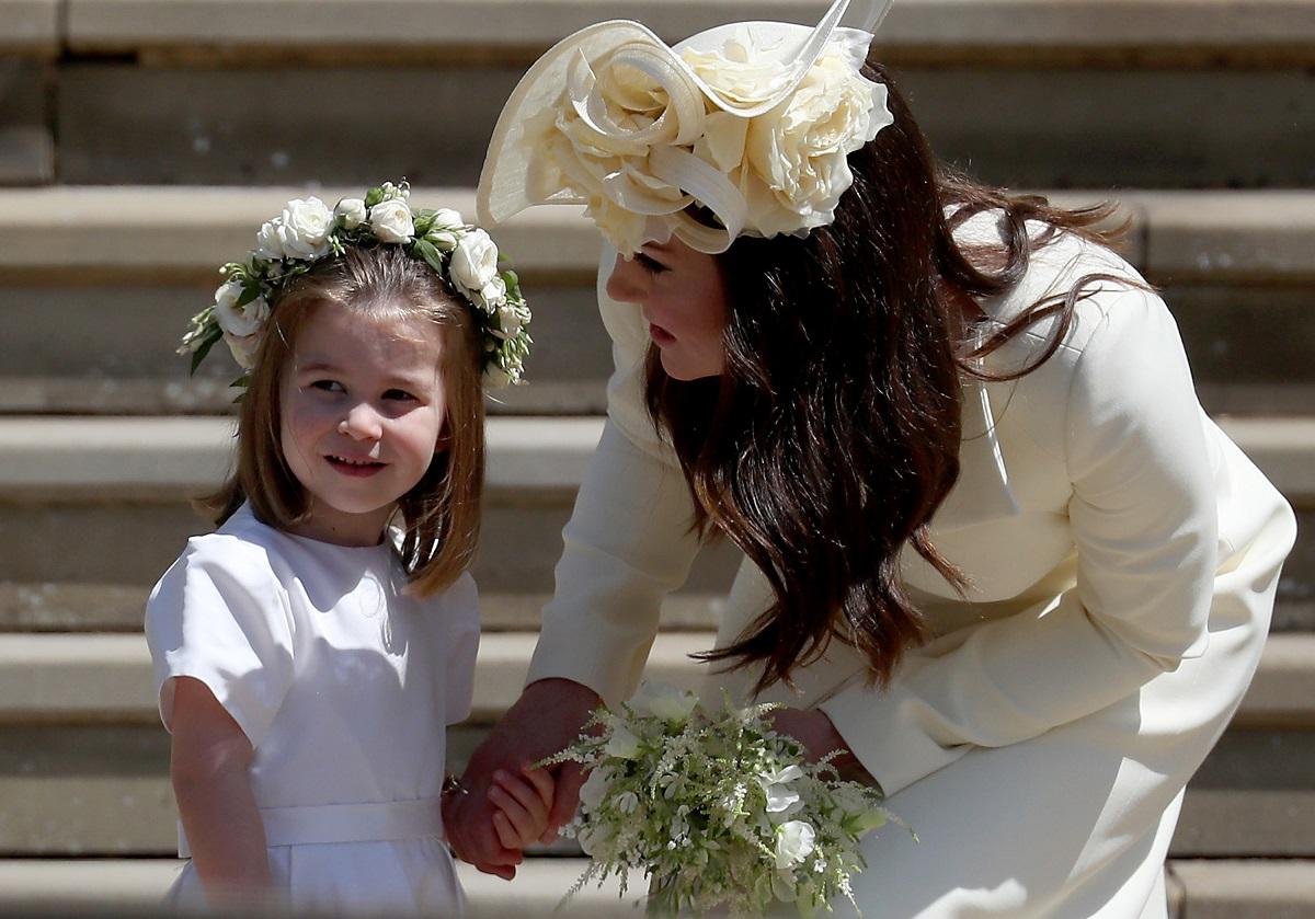 Prințesa Charlotte într-o rochiță albă în timp ce poartă pe cap o coroniță de flori, iar mama sa, Kate Middleton o ține de mână