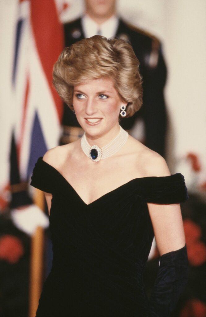 Prințesa Diana într-o rochie neagră pe umeri în timp ce zâmbește după ce a participat la un eveniment de la Casa Albă în 1985