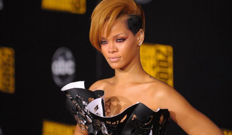 Portret al artistei Rihanna având părul tuns scurt și vopsit blond în timp ce pozează pe covorul roșu la American Music Awards din 2009