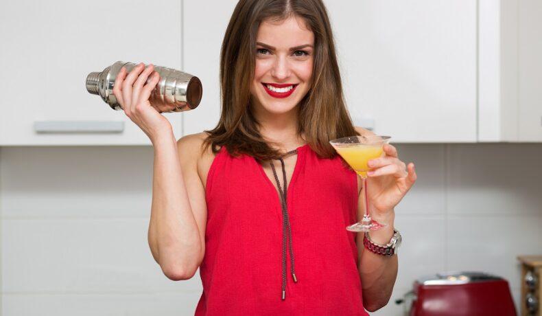 O femeie frumoasă care se află într-o bucătărie și ține în mână un pahar cu un cocktail fără alcool și un shaker