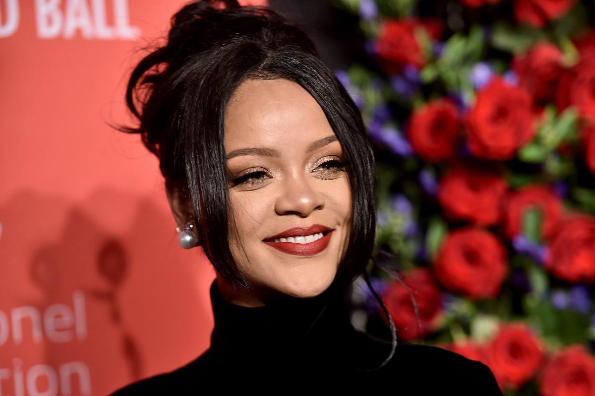 Artista Rihanna care a devenit miliardară purtând o rochie neagră pe gât și părul prins într-un coc lejer în timp ce zâmbește la cameră și se află pe covorul roșu