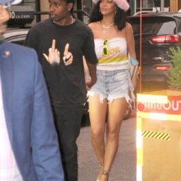 ASAP Rocky îmbrăcat în negru alături de Rihanna care poartă o pereche de blugi, un top alb și o pălărie roz cu puf