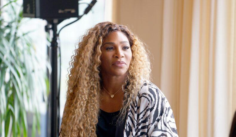 Portret al sportivei Serena Williams cu părul lung și blond în timp ce poartă o bluză albă cu imprimeu florel negru și ia parte la un interviu în New York în anul 2019