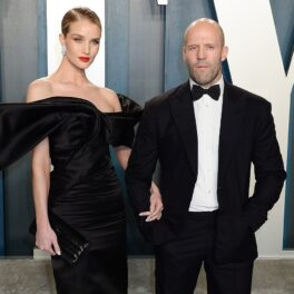 Rosie Huntington-Whiteley într-o rochie neagră lungă cu umeri bufanți alături de logodnicul său Jason Statham îmbrăcat la frac negru în timp ce pozează pe covorul roșu la petrecerea ținută cu ocazia Premilor Oscar în anul 2020