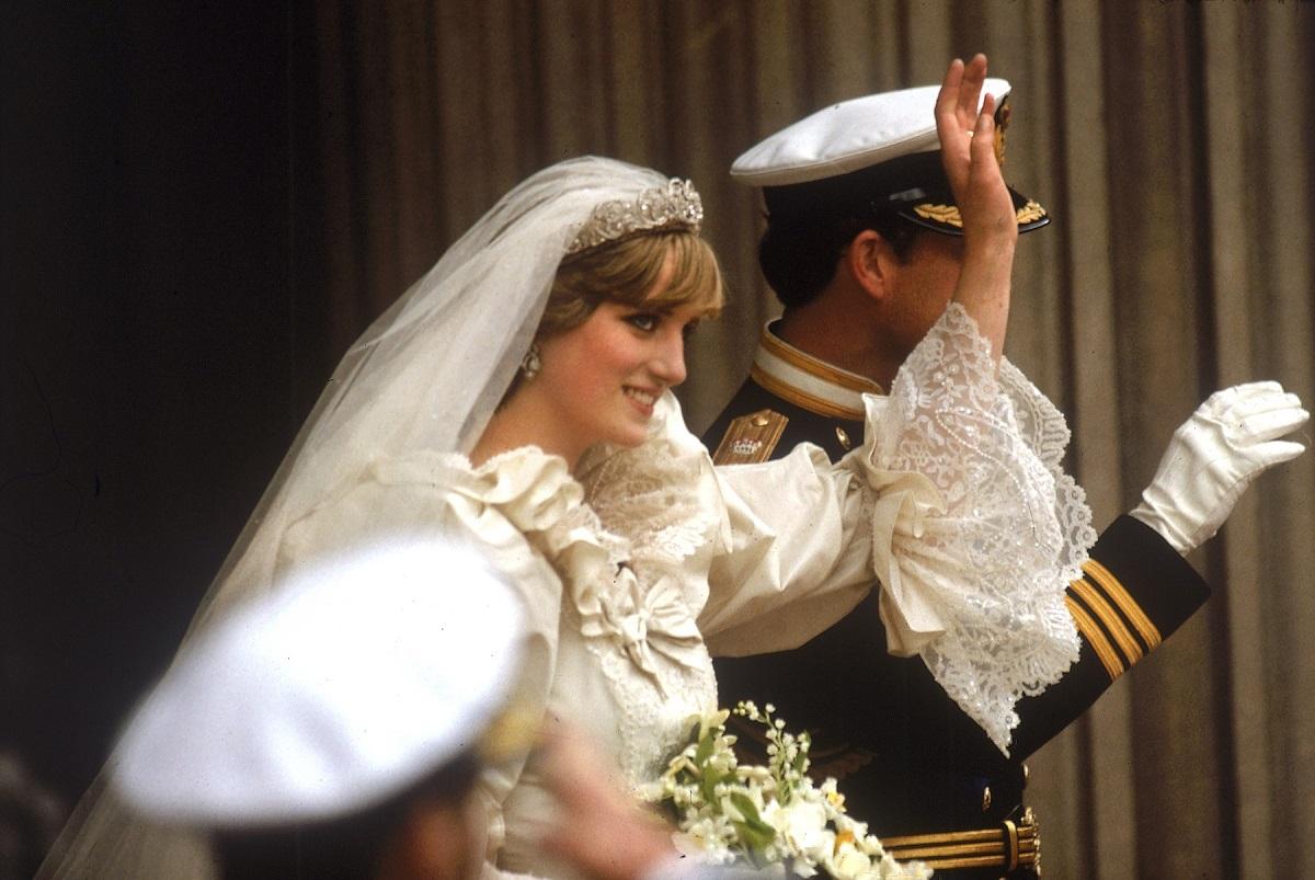 Prințesa Diana în rochie de mireasă alături de Prințul Charles în uniformă, în timp ce fac cu mâna publicului la nunta regala din 1981