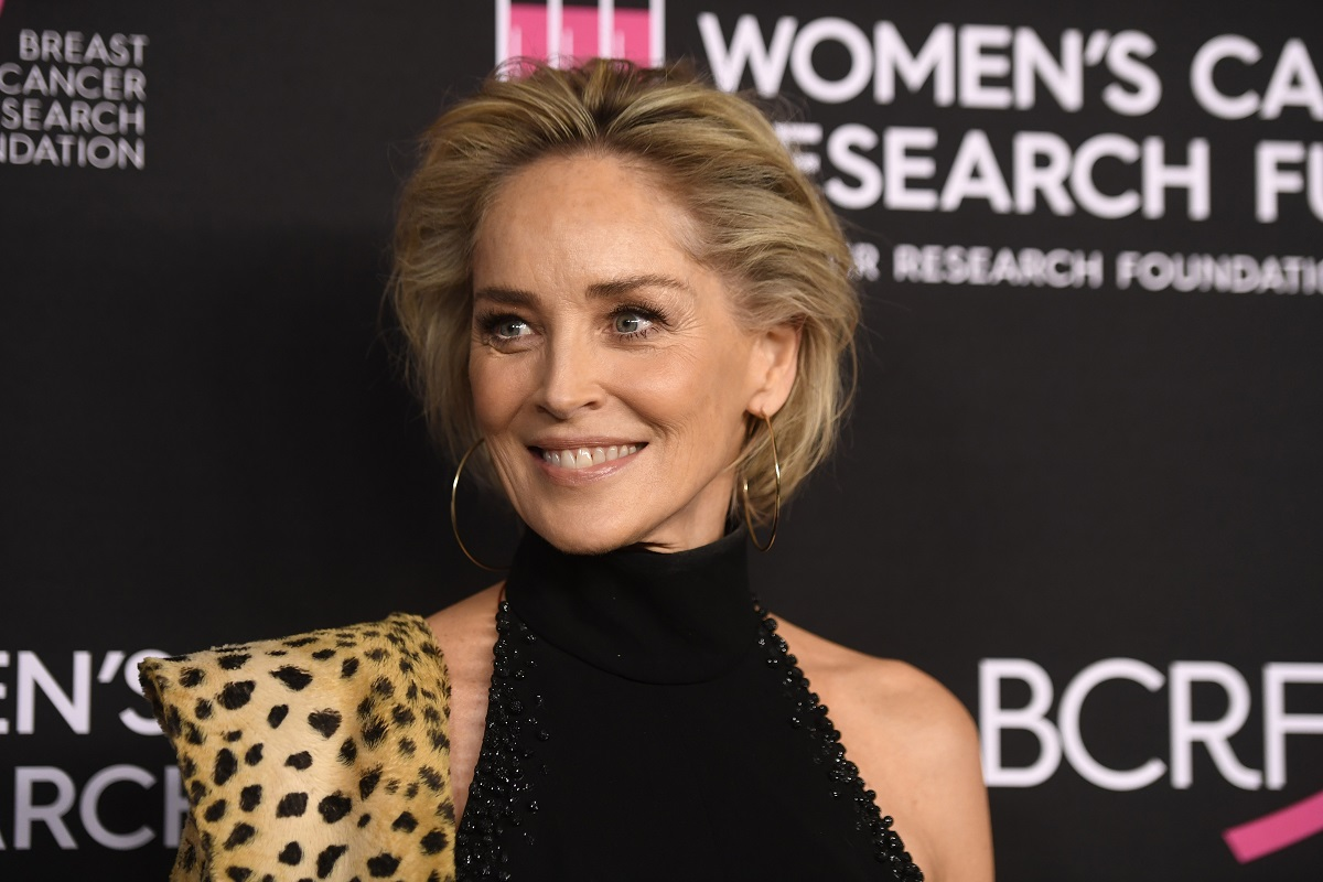Sharon Stone purtând o rochie neagră pe gât și o haină de blană cu imprimeu de leopard în timp ce pozează pe covorul roșu