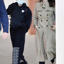 Shiloh Jolie-Pitt îmbrăcată casual în hanorac negru și pantaloni de aceeași culoare, alături de mama sa, Angelina Jolie care poartă un trench crem în timp ce sosesc pe aeroportul din Veneția