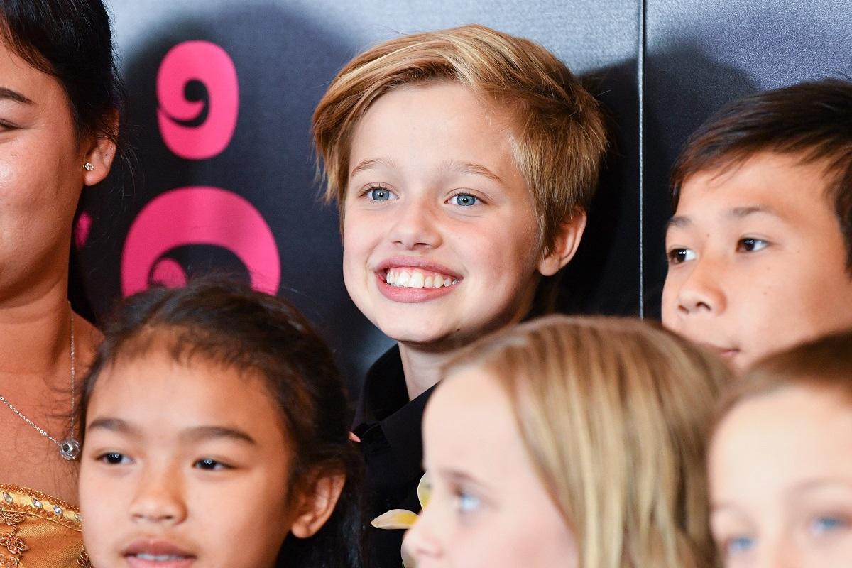Shiloh Jolie-Pitt în timp ce zâmbește larg într-o printre mai mulți copii în timp ce se află la premiera filmului First They Killed My Father din 2017
