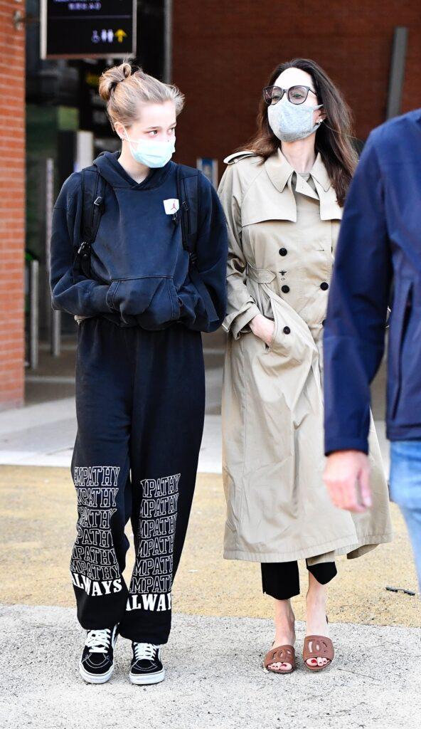 Shiloh Jolie-Pitt într-un hanorac și o pereche de pantaloni negri alături de mama sa, Angelina Jolie care poartă un trench crem în timp ce merg împreună