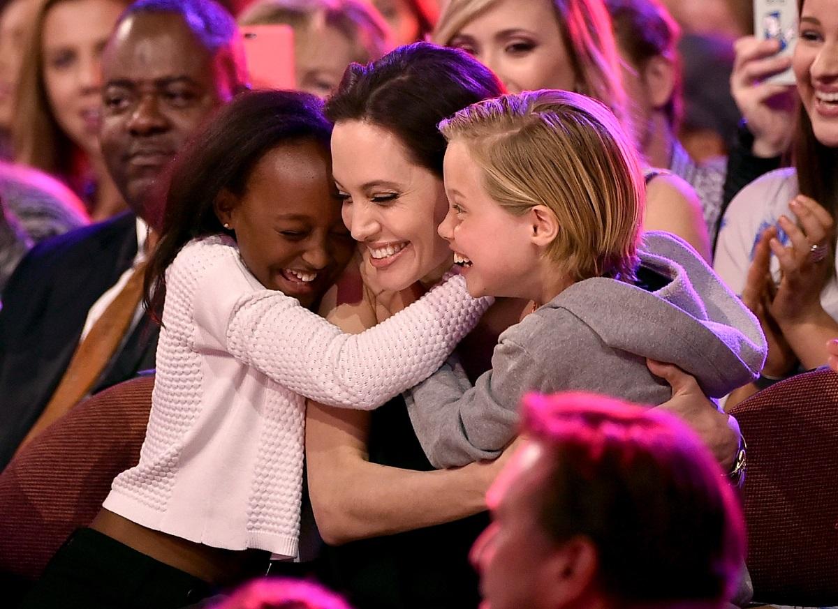 Angelina Jolie într-o rochie neagră în timp ce este îmbrățișată de două dintre fiicele sale, Zahara și Shiloh Jolie-Pitt