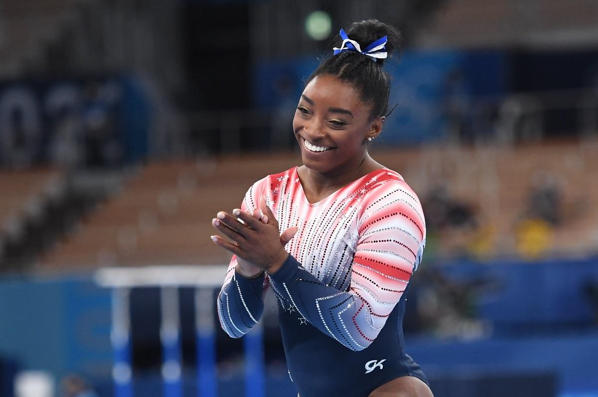 Simone Biles în costumul de gimnastă al americii în timp ce își aplaudă colegele la Jocurile Olimpice de la Tokyo
