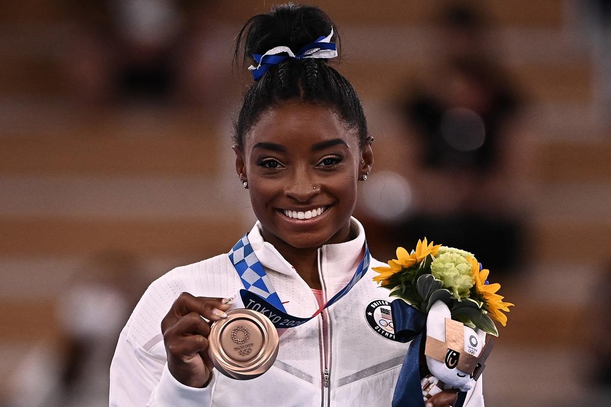 Gimnasta Simone Biles în timp ce ține în mână un buchet de flori și o medalie de argint în cadrul Jocurilor Olimpice de la Tokyo