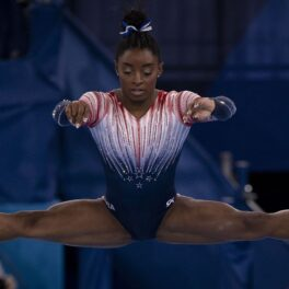 Simone Biles în timp ce execută o săritură în șpagat și poartă costumul echipei Statelor Unite ale Americii
