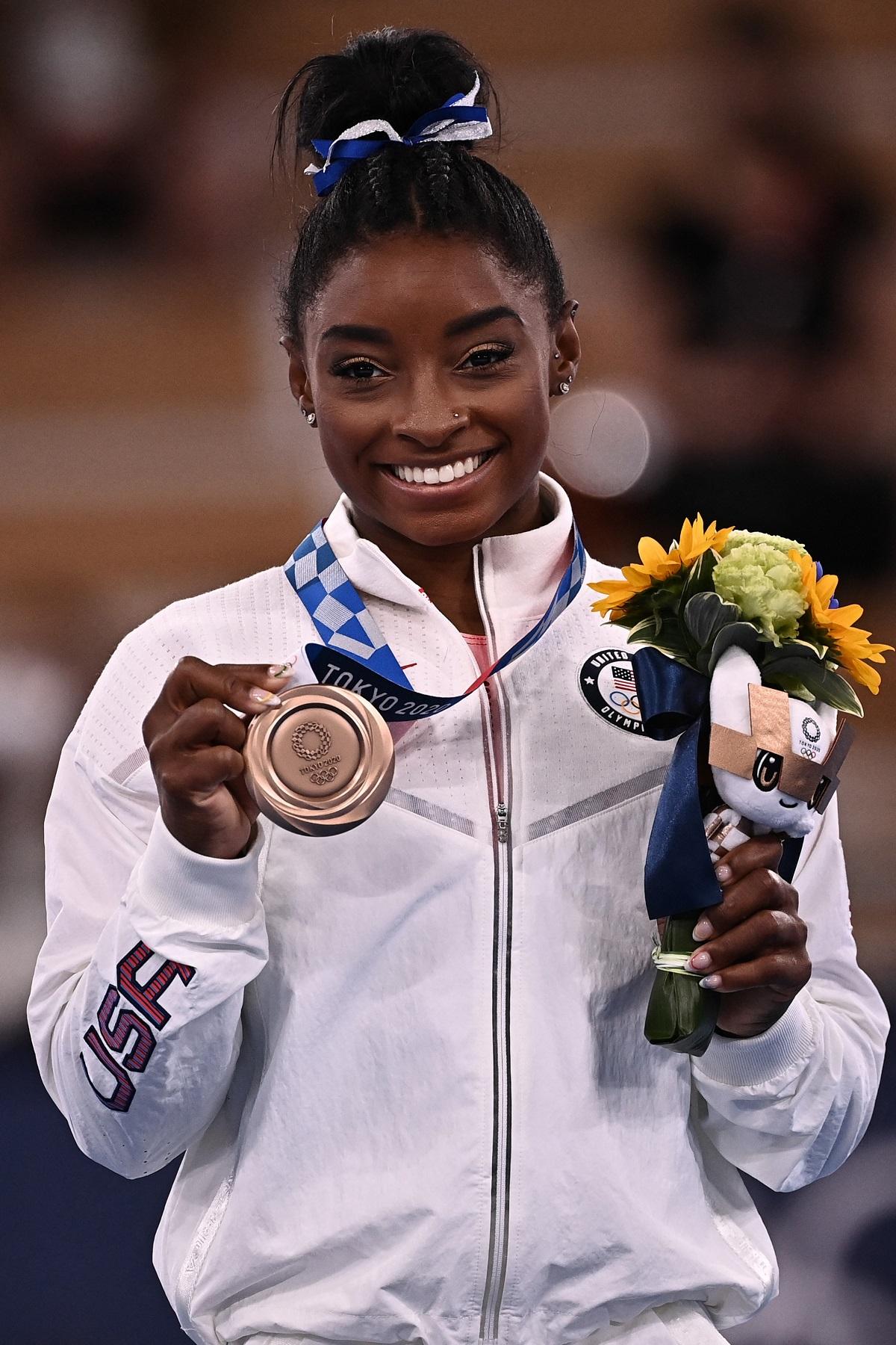 Simone Biles în timp ce poartă o bluză albă de treining și ține în mână un buchet de flori și o medalie de bronz la Jocurile Olimpice de la Tokyo