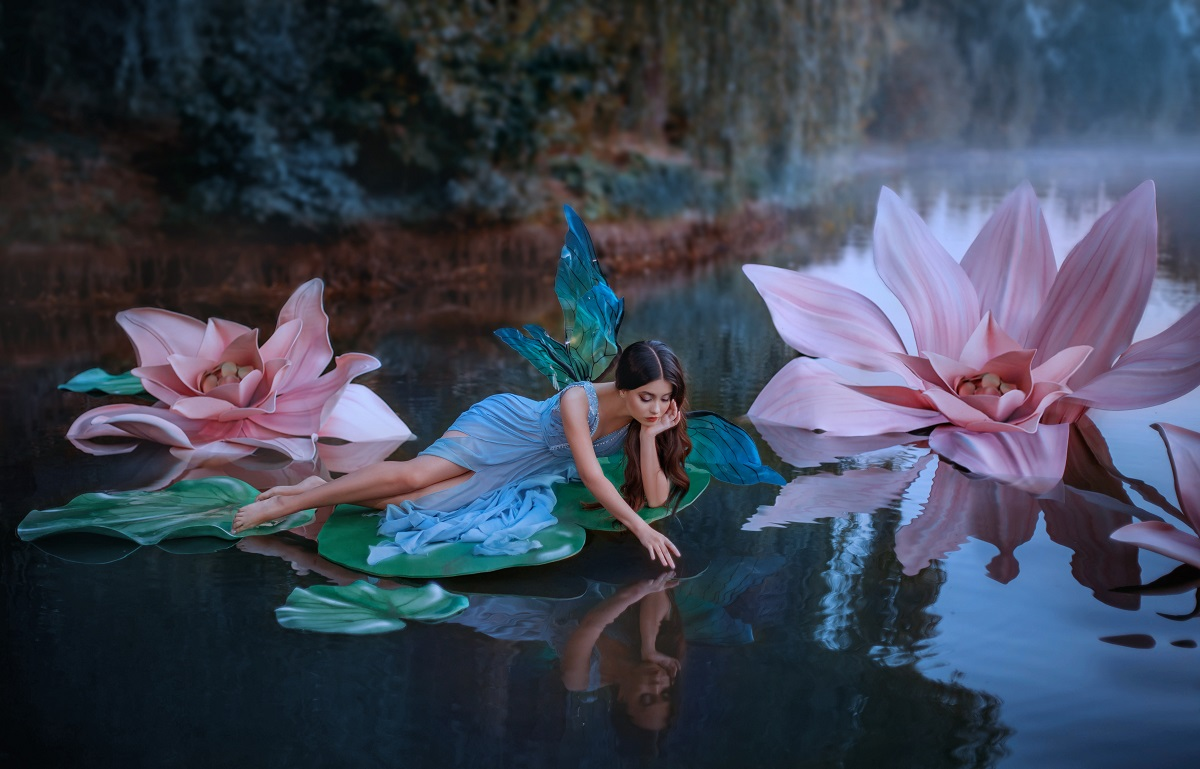 O femeie frumoasă care este zână și poartă o rochie albastră în timp ce stă pe o frunză de nufăr și mângâie cu mâna apa din lacul pe care se află, reprezentând una din acele zodii singuratice