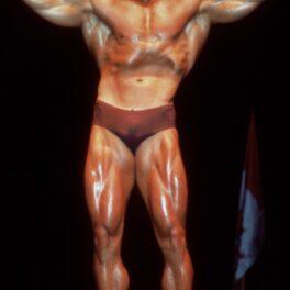 Arnold Schwarzenegger, la o competiție de bodybuilding din anii 1980. Mușchii mari, dați cu ulei, slip de culoare maro, fundal negru