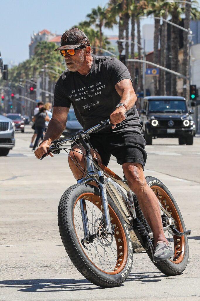 Arnold Schwarzenegger pe bicicletă, în Santa Monica, California. El e îmbrăcat în negr, bicicleta e cu argintiu, negru și portocaliu, pe fundal stradă și mașini