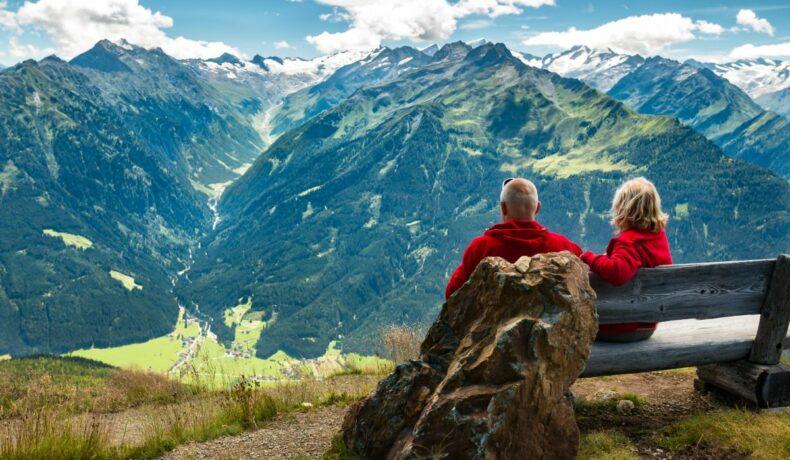 Un cuplu senior stă pe o bancă în Alpii austrieci și demonstează că bătrânețea este o etapă fericită a vieții