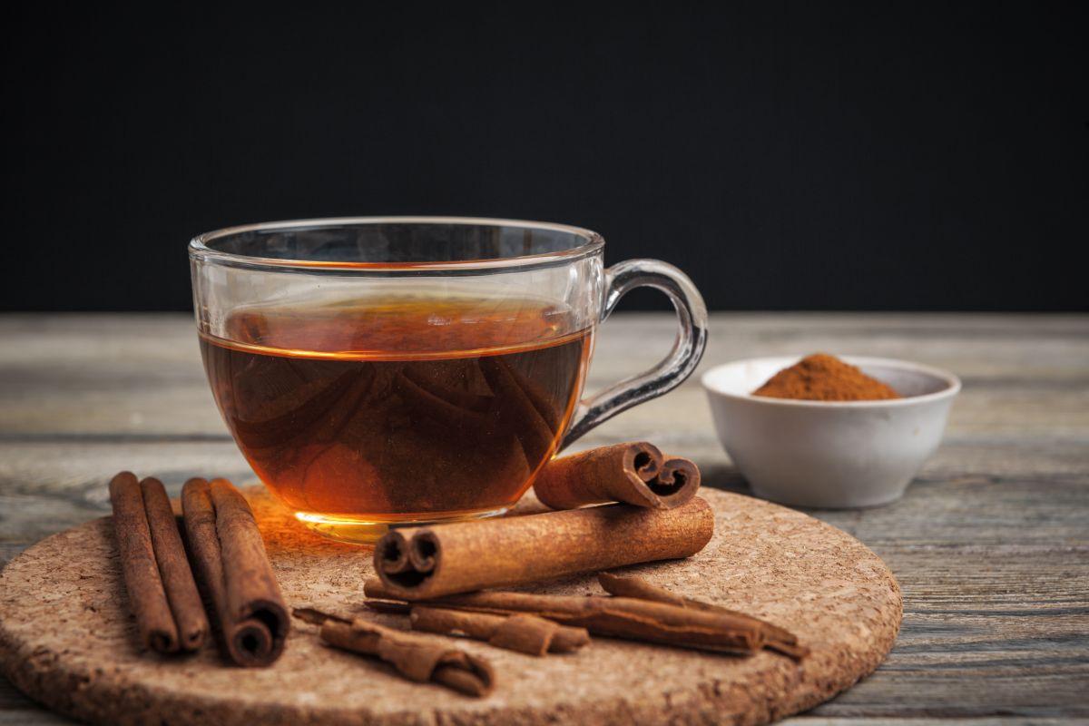 O cană cu ceai de scorțișoară, așezată pe un suport din plutp, alături de batoane și pudră de scorțișoară