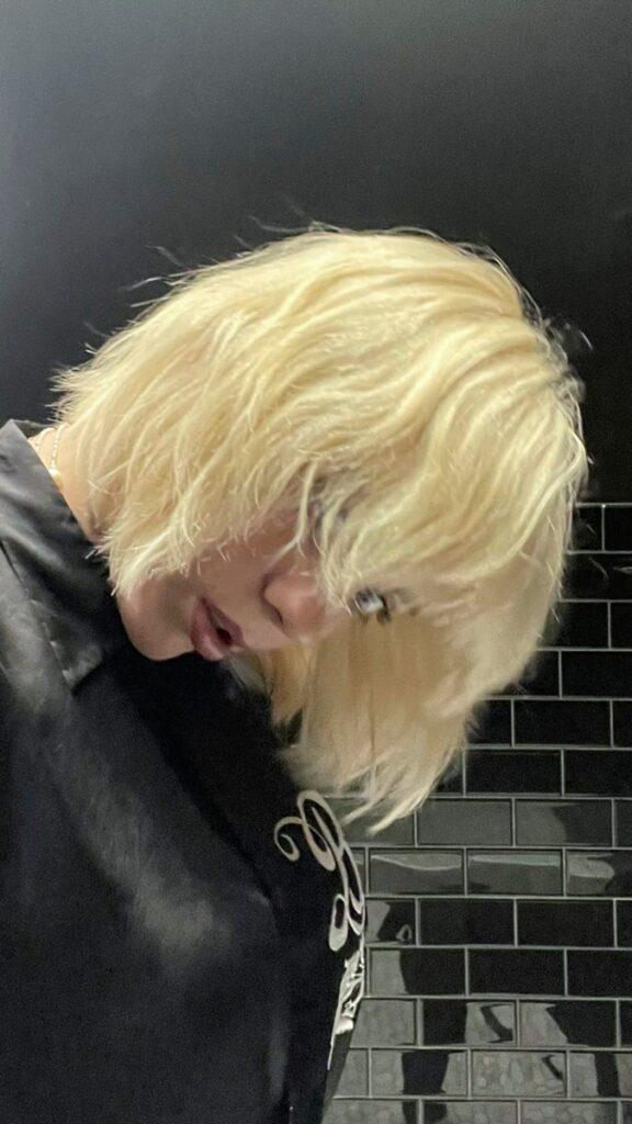 Billie Eilish și-a tuns părul blond până la mandibulă, cu breton. Îmbrăcată cu negru, fundal cu negru