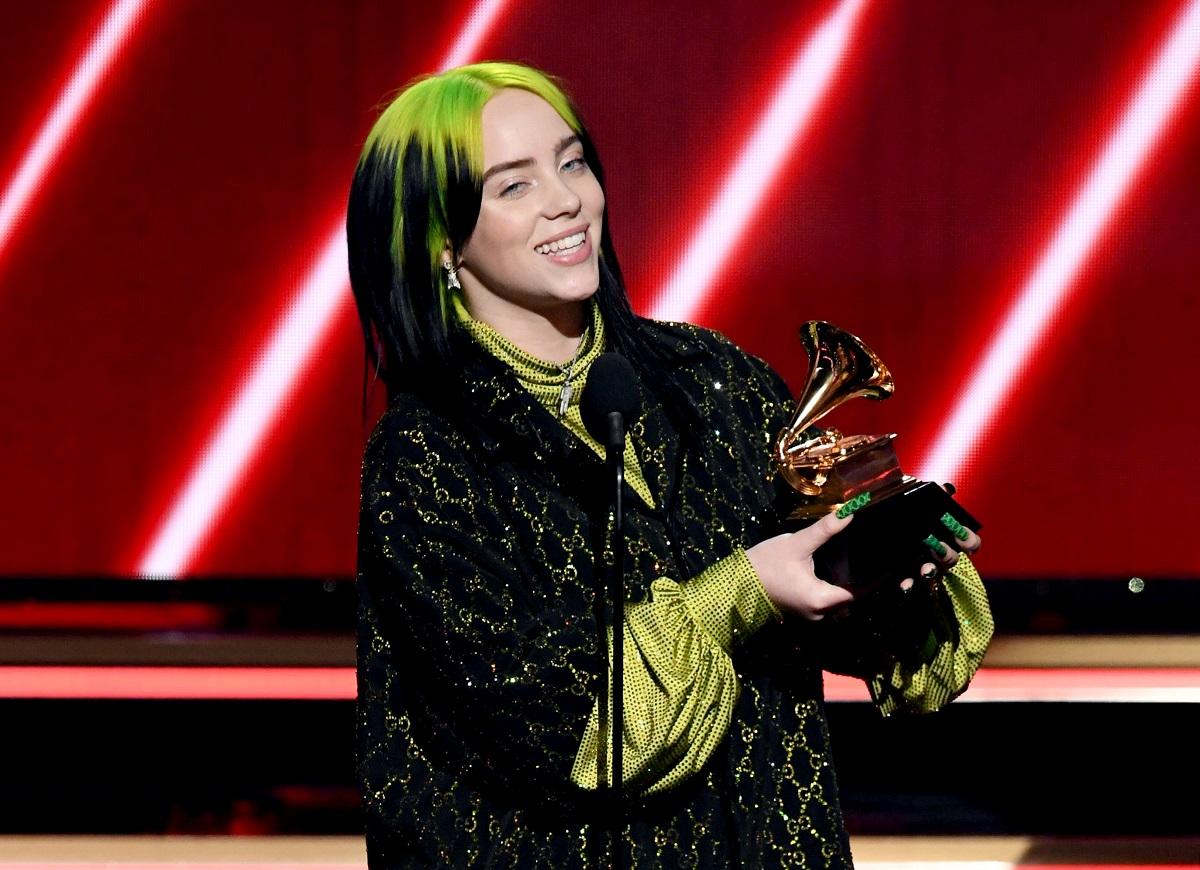 Billie Eilish, scena Premiilor Grammy, la cea de-a 62-a editie, în anul 2020. Eilish a purtat o bluză neagră deasupra, bluză verde dedesubt, are părul verde cu negru și un premiu Grammy în mână, cu fundal roșu
