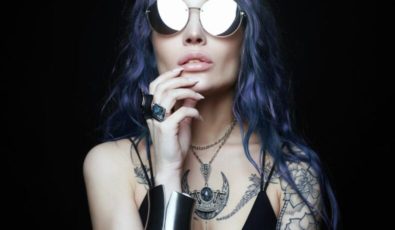 O femeie cu părul lung, albastru, care poartă ochelari de soare și bijuterii masive, are imprimate pe corp tatuaje.