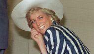Prințesa Diana, într--un costum cu dungi albe și albastru închis, pălărie albă. Zâmbește și se uită la cameră, pe fundal e un perete bej