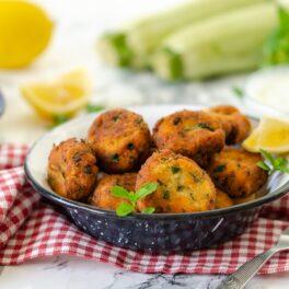 Chiftele de dovlecei rumenite și așezate în bolul de servire, alături de un bol cu cu sos de iaurt și brânzeturi și doi dovlecei
