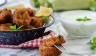 Chiftele de dovlecei în bol de servire, alături de două chiftele glazurate cu sos și bolul cu sos de iaurt și brânzeturi