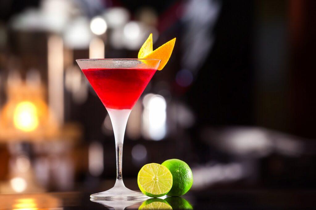 Un pahar pe un bar care este umplut cu un coktail cosmopolitan și decorat cu o felie de coajă de portocală