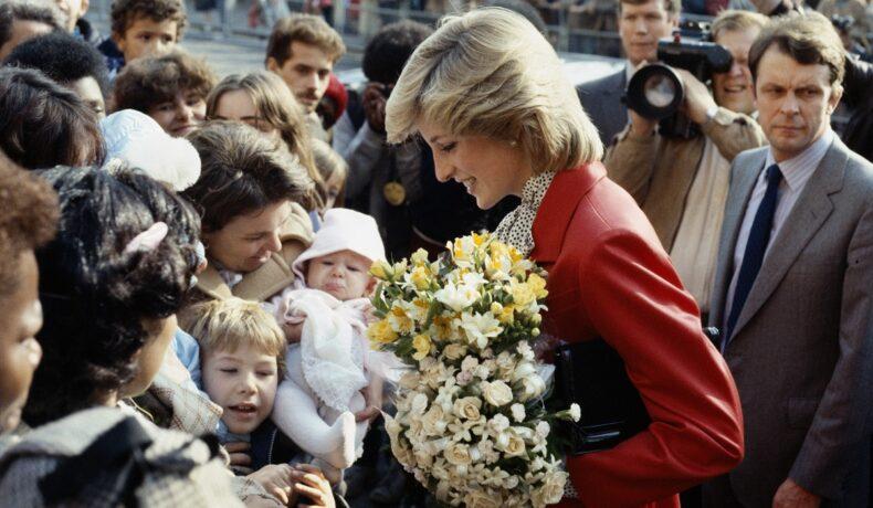 Într-o vizită în Brixton, 1982, Prințesa Diana a purtat un osum roșu pe care le-a accesorizat cu o geantă neagră. Surprinsă în mulime, cu buchete de flori în mână