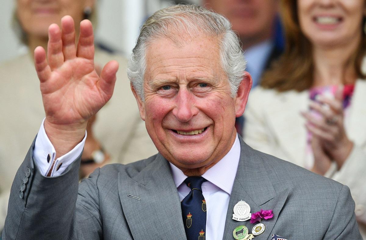 Prințul Charles a aprticipat la Royal Cornwall Show în iunie 2018. A purtat un costum gri, cu o cămașă albă, cu butonieră din flori. Face cu mâna la public, are o mulțime în spate