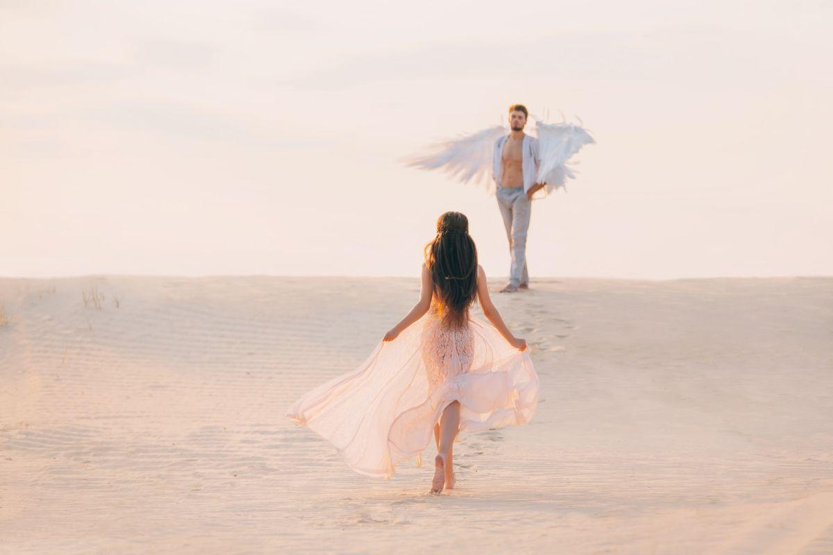 O femeie cu părul lung, îmbrăcată în alb, pășeste către un bărbat, care are aripi de îngeri.