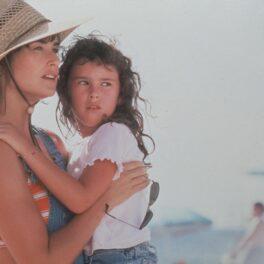 Demi Moore și fiica ei, Rumer Willis, în filmul Striptease. Ea poartă pălărie de paie, bluză în dungi cu galben și verde, salopetă de blugi. Rumer poartă salopetă de blugi și bluză albă, fundal cu cer