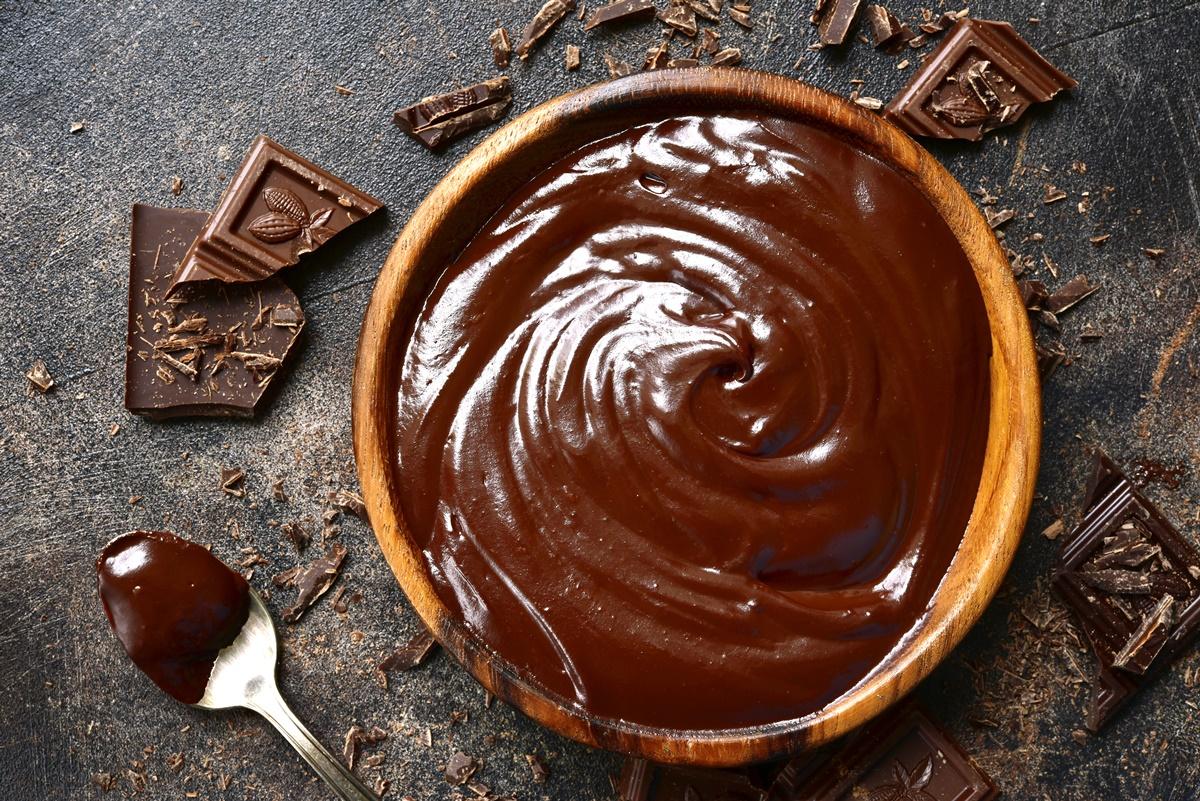Cremă ganache de ciocolată într-un bol de lemn, alături de bucăți de ciocolată și o linguriță cu cremă