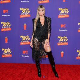 Heidi Klum, MTV Movie Awards, 2021, pe covorul roșu, a purtat o ținută neagră. Ținuta avea o bluză cu mâneci lungi și o fusta din plasă, cu o crăpătură mare, și cizme înalte negre. Fundal roșu cu albastru