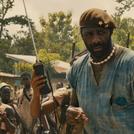 Idris Elba în filmul Beasts of No Nation. Poartă o bluză din blugi, cu decolteu, și o baretă. Fundal tropical cu război