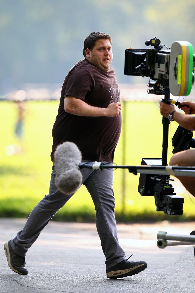 Jonah Hill surprins pe platoul de filmare al Get Him To The Greek, în timpul filmărilor. Actorul alerga în blugi și tricou, cu fundal gri cu galben