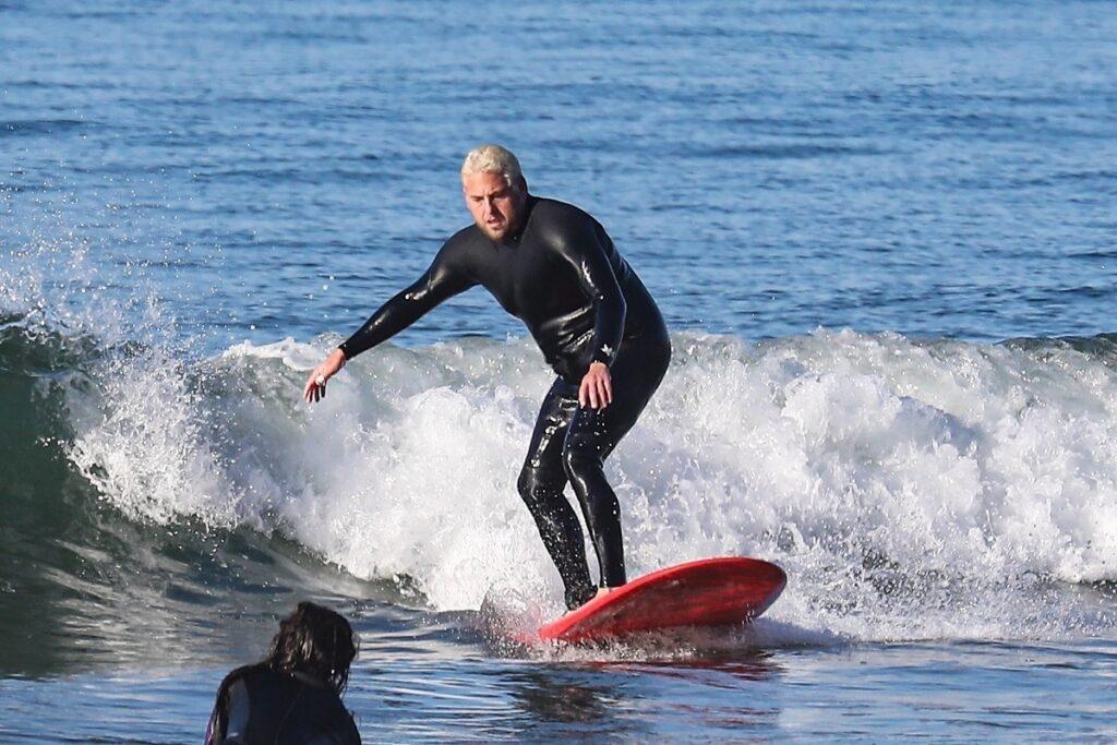 Jonah Hill la mare, în timp ce face surfing. Placa lui e roșie și costumul lui e negru, cu un val pe fundal