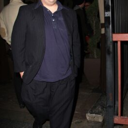 Jonah Hill surprins de paparazzi în West Hollywood, în anul 2008. Îmbrăcat în costu negru, cămașă albastru închis, fundal cu stradă
