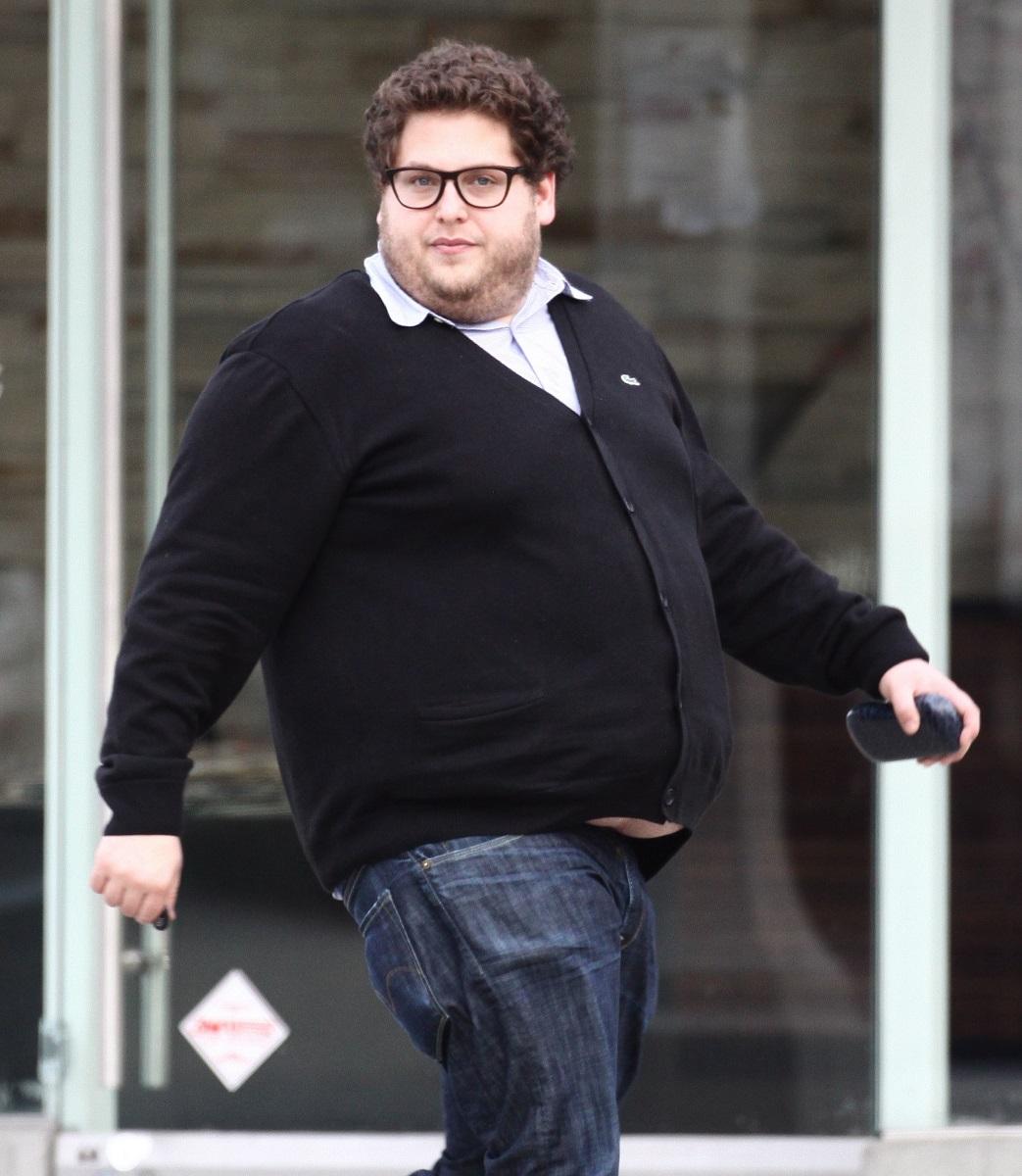 Jonah Hill, străzile din Los Angeles, îmbrăcat în blugi, cămașă albă, pulover negru, mai gras. Fundal cu ferestre gri cu alb